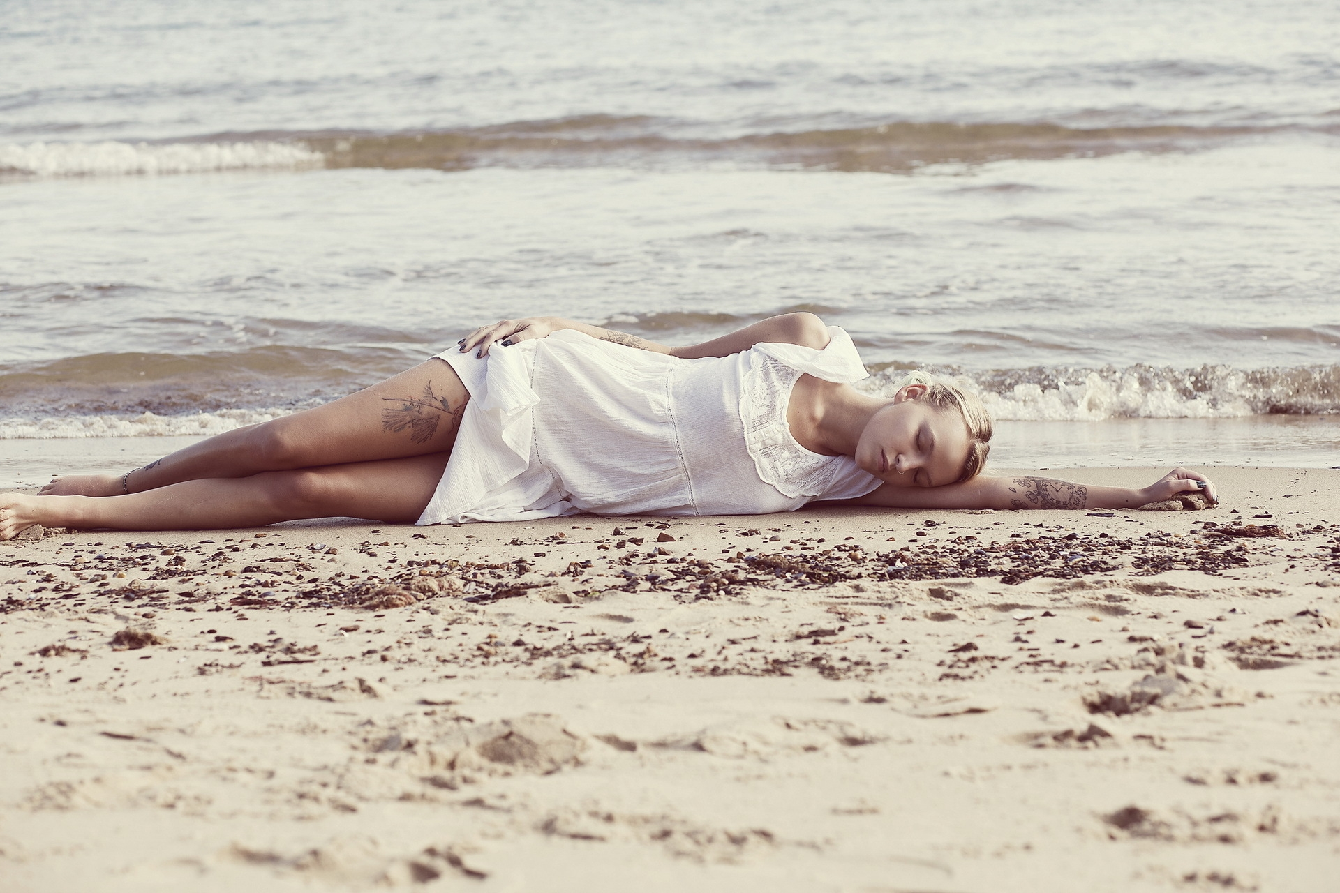 Тату у девушки на песке